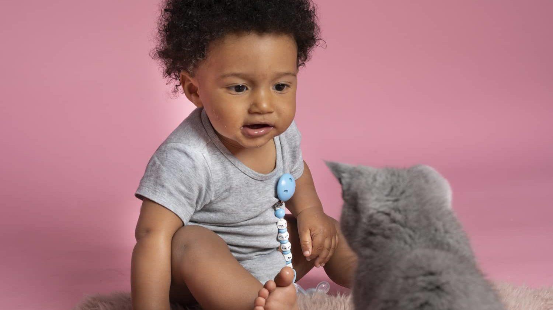 EIne Katze und ein Kind mit Schnullerkette